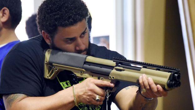 Homem segura arma na feira realizada na Flórida