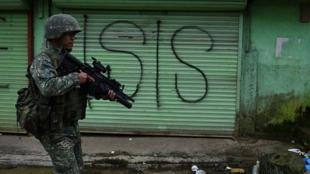APhilippine Marine walks past graffiti during a patrol along a deserted street at the frontline in Marawi, on the southern island of Mindanao on 22 July 2017.