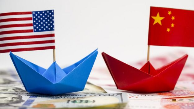 Mockup with two paper boats and the flags of the United States and China.