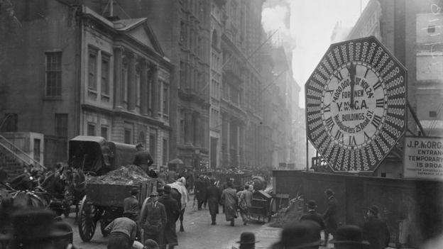 Vagones en las calles de Manhattan pasando frente un reloj con el anuncio del proyecto de donaciones de YMCA