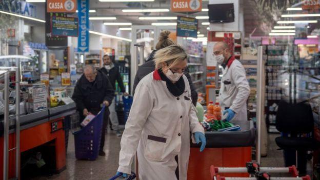 Italianos con mascarillas en un supermercado en Italia