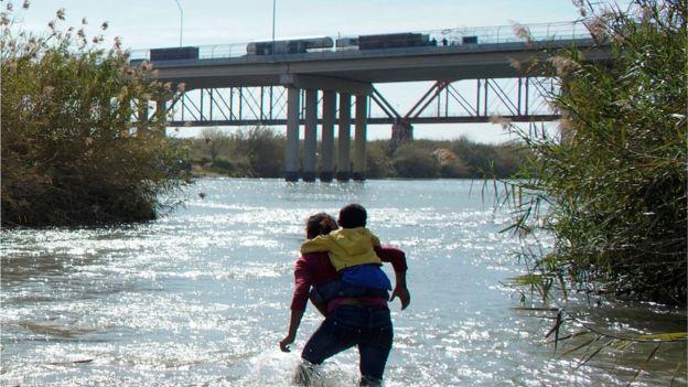 Una mujer con un niño tratando de cruzar el Río Bravo, frontera natural entre México y Estados Unidos.