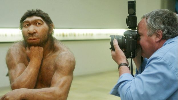Una figura de neandertal siendo fotografiado.