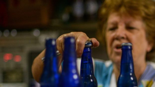 Una mujer abre unas cervezas