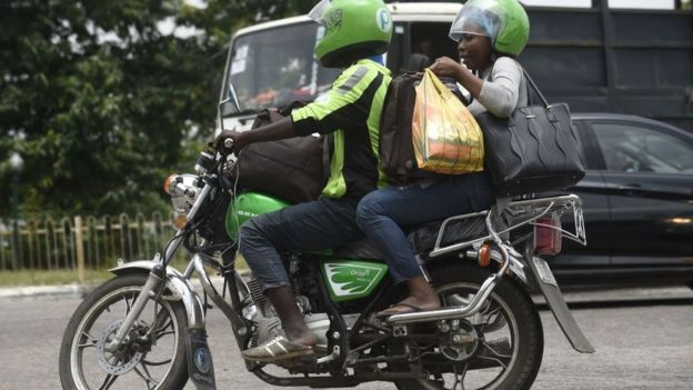 A Nigerian motorbike rider drive through traffic gridlock in Lagos with his passenger
