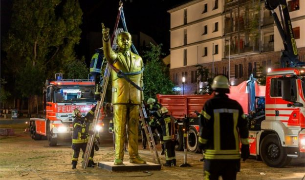 Firefighters lift the golden statue using a crane under cover of darkness