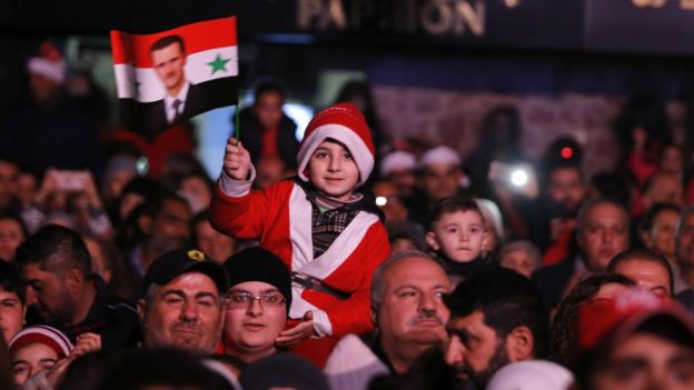 A child waves a flag of Syrian President while wearing a santa costume