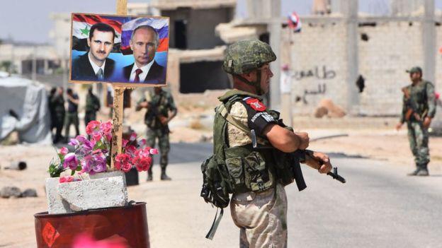 İdlib'in doğusundaki Ebu Duhur geçişine Esad ve Putin posterleri asılı.