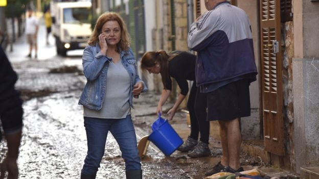 Residents remove water from their homes in the town of Sant Llorenç on the Spanish island of Majorca, 10 October 2018