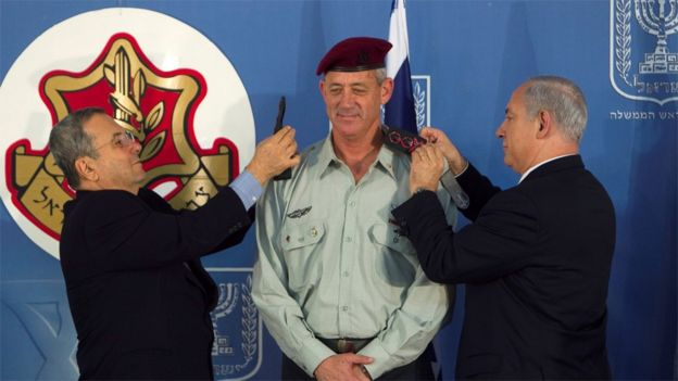 El ministro de Defensa de Israel Ehud Barak (izq) y el primer ministro Benjamín Netanyahu (der) cambian las charreteras del nuevo jefe del estado mayor de las IDF, Benny Gantz. 14 de febrero de 2011