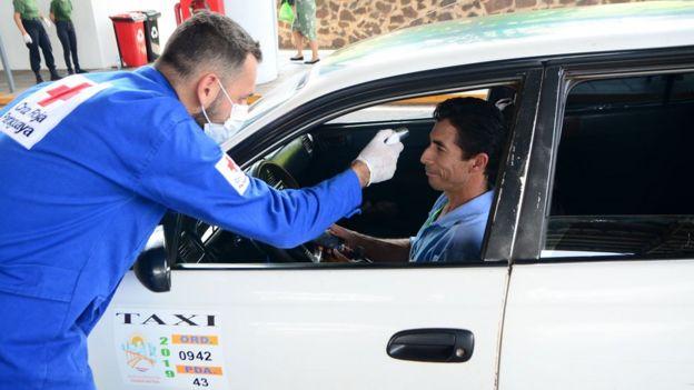 Un representante de la Cruz Roja le toma la temperatura a un taxista