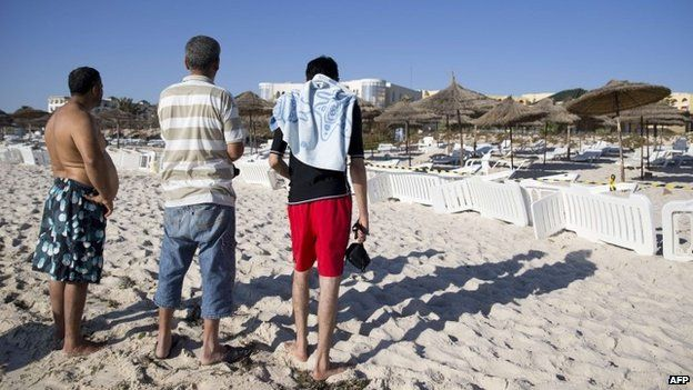 Tunisians stand on the beach of the Riu Imperial Marhaba Hotel in Port el Kantaoui, on the outskirts of Sousse south of the capital Tunis