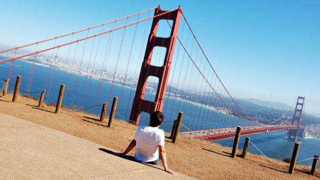 A boy looks at the Golden Gate bridge