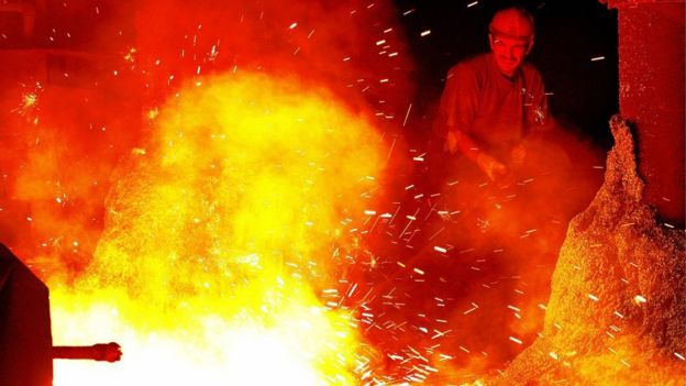 A steel worker works in front of giant iron melting pot in Kardemir Iron and Steel Factory in Karabuk, north-western Turkey (26 August 2005)