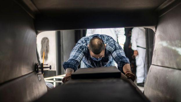 Hombre junto a un cajón fúnebre.
