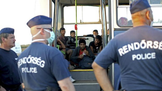 Hungarian police officers stand outside a bus with migrants at a migrant collection point in Roszke, Hungary - 12 September 2015