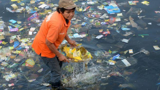 Imagem mostra mulher retirando plástico do oceano