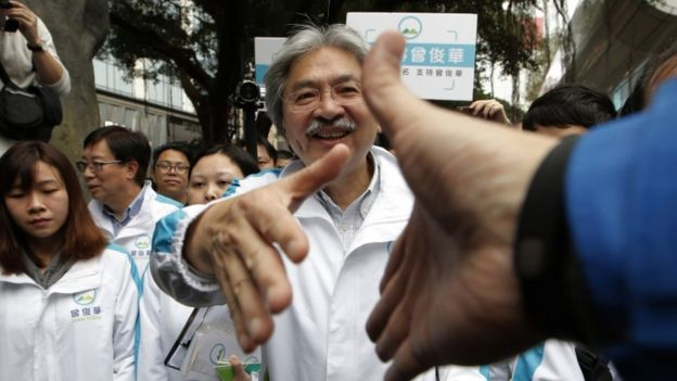 In this Saturday, 18 March 2017 photo, Hong Kong chief executive candidate former Financial Secretary John Tsang shakes hands with supporters during an election campaign in Hong Kong