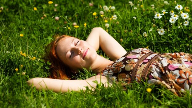 Generic image of a woman sunbathing on flower-covered grass