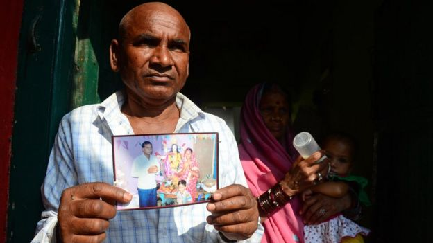 Un hombre sostiene la foto de Janki Bai, una mujer que murió en la esterilización colectiva.