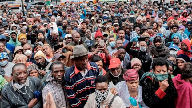 Informal vendors gather in front of a municipal office building in Braamfontein, Johannesburg, on April 8, 2020, as they try to obtain a permit for working during the 21 days national lockdown that started on March 27, 2020, in an attempt to halt the spread of the COVID-19 coronavirus outbreak