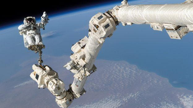 A spacewalking astronaut attached to a robotic arm