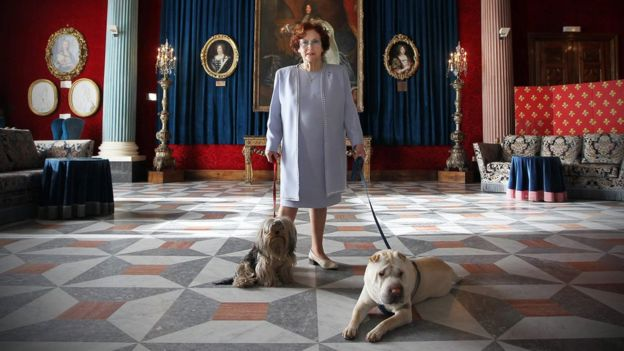 Jeanne Augier, owner of the famous Negresco hotel, poses with her dogs in the Versailles lounge of the palace in Nice, south-eastern France, 13 January 2011