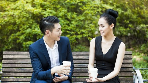 Una pareja joven se toma un café en un banco del parque.