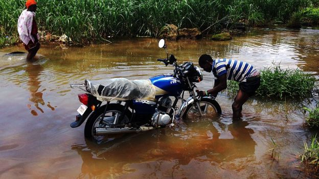 A man washes his motorbike in a flooded road in Liberia