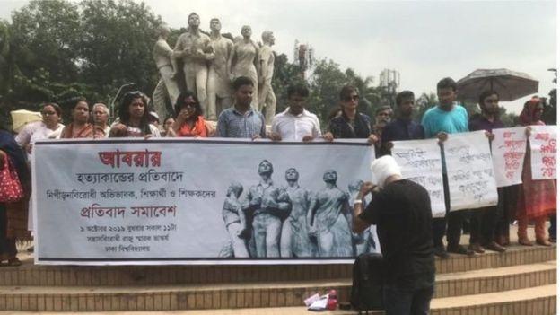 ঢাকা বিশ্ববিদ্যালয়ের রাজু ভাস্কর্য প্রাঙ্গণে বিশ্ববিদ্যালয়ের শিক্ষার্থী এবং শিক্ষকরা বিক্ষোভ করছে