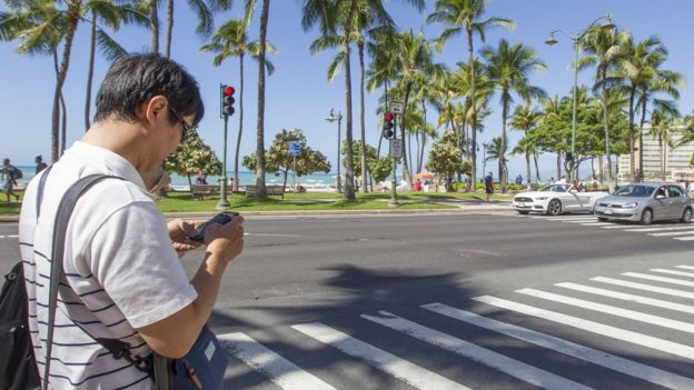 Man using cell phone in the streets of Hawaii.
