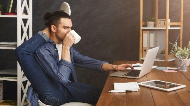 Un hombre contorsionista sentado frente a una laptop.