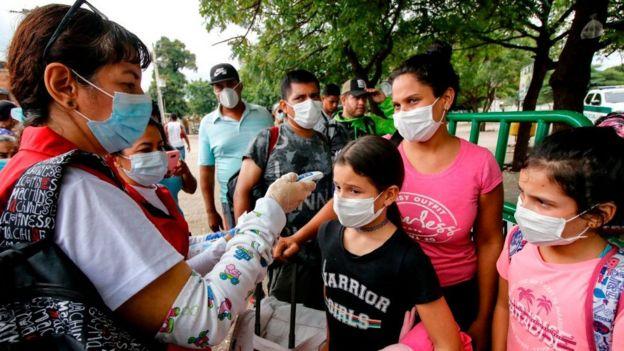 Mujer tomándole la temperatura a niños en la frontera entre Venezuela y Colombia