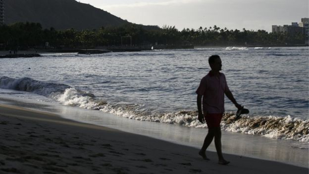 Un hombre camina por Playa Waikiki, Honolulu.