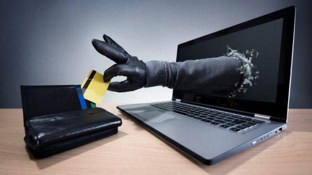 Una mano con guante sale de una pantalla de computadora para robar una tarjeta de crédito.