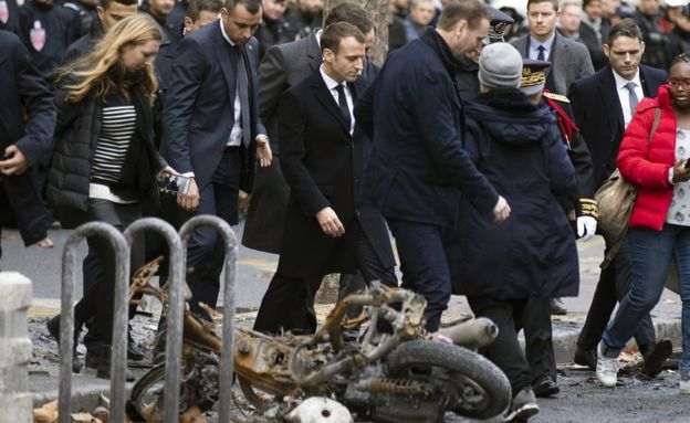 """French President Emmanuel Macron (centre) assesses damage following the """"Yellow Vests"""" protest a day earlier, next to the Champs Elysee in Paris, France, 2 December 2018"""