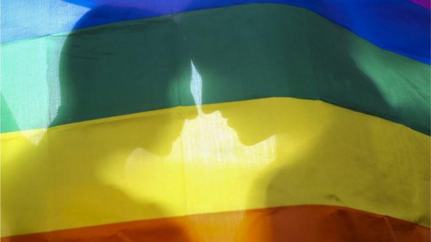 Duas mulheres atrás de bandeira do arco-íris