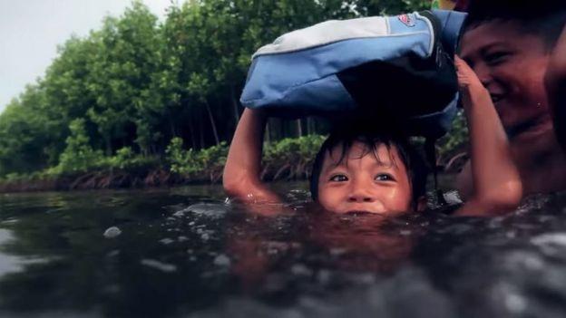 Seorang anak harus mengarungi air untuk pergi ke sekolah
