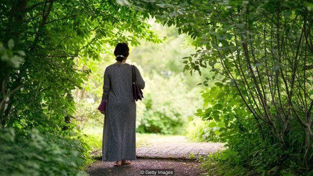 Mulher caminhando em parque
