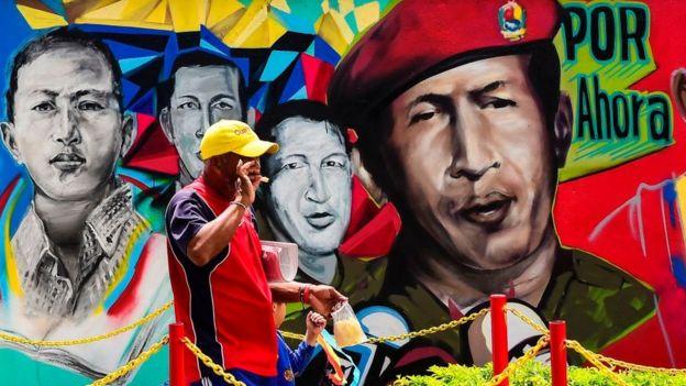 hombre frente a mural de Chávez