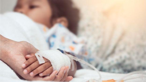 Mão de adulto segura a mão de uma criança hospitalizada