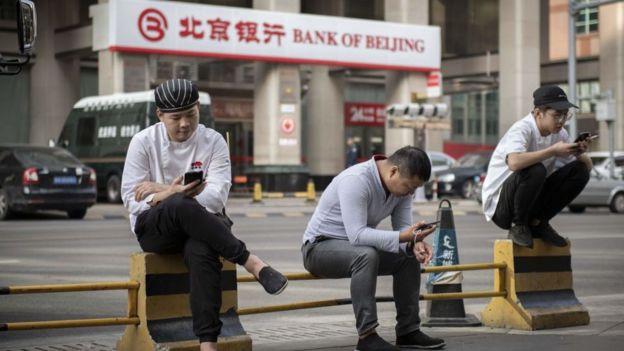 Ciudadanos mirando el teléfono móvil en China.