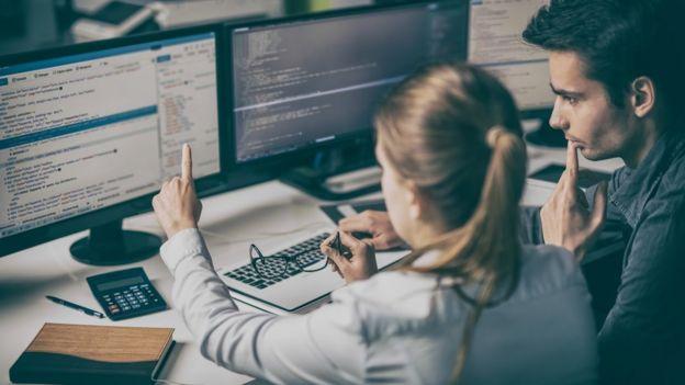 Mulher e homem olham para tela de computador