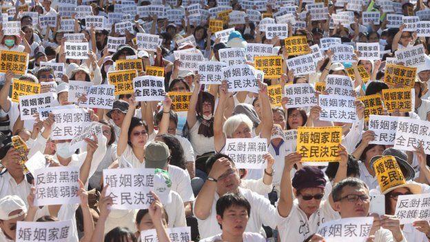 """下一代幸福联盟号召反对同性婚姻合法化的民众身穿象征""""光明正面诉求""""的白衣,手持大会发放的标语,11月17日同婚法案审理时,聚集在立法院外抗议。"""