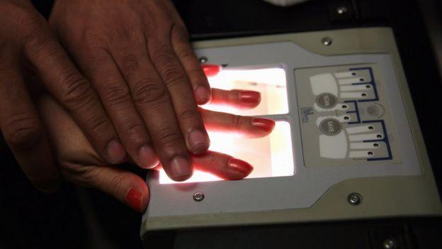 美國當局正在紀錄一名中國移民的手指模