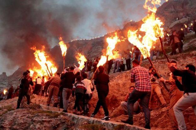 في دهوك بكردستان العراق، يحمل المئات من الشباب والشابات المشاعل ويصعدوا إلى قمة جبل عقرة (آكري) إحياء لتقليد كاوا الحداد قبل أكثر من ألفي عام. 20 مارس/آذار 2018