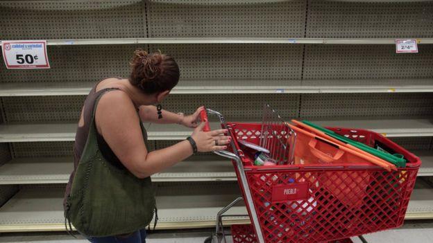 Mulher empurra carrinho de supermercado ao lado de prateleiras vazias
