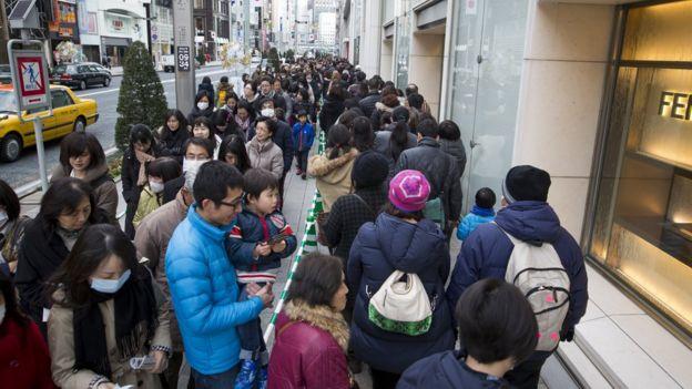 fila na frente de loja de departamento no Japão