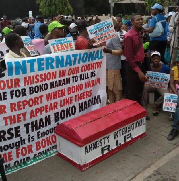People carry a symbolic coffin, 'amnesty international R.I.P' written on it, during a protest staged against Amnesty International's (AI) 2017 annual report near the AI's office in Abuja, Nigeria on March 22, 2017.