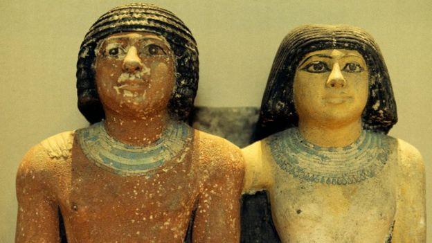 تمثال لشخص من عصر الدولة القديمة وإلى جوراه زوجته وتضع مساحيق التجميل والشعر المستعار